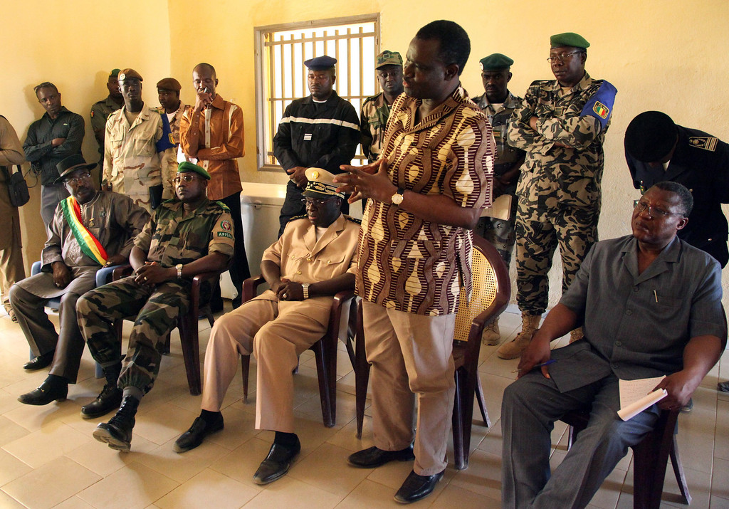 ". Burkinabe President of the Economic Community of West African States (ECOWAS) Commission, Kadre Desire Ouedraogo (4th R), speaks to military officers during a visit to Franco-African troops in Gao on April 21, 2013. Ouedraogo encouraged Franco-African troops in Mali to ""not release the pressure\"" against the Islamists armed groups. AFP PHOTO /STRSTR/AFP/Getty Images"