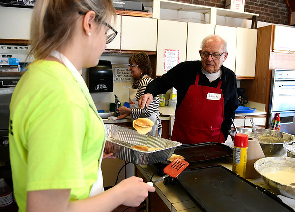 3/9/2019 Mike Orazzi | Staff Volunteer Dick Rease flips pancakes to Bo Wicklund during the Pancake Breakfast & Maple Sugaring program at the New Britain Youth Museum & Hungerford Nature Center on Saturday in Kensington.