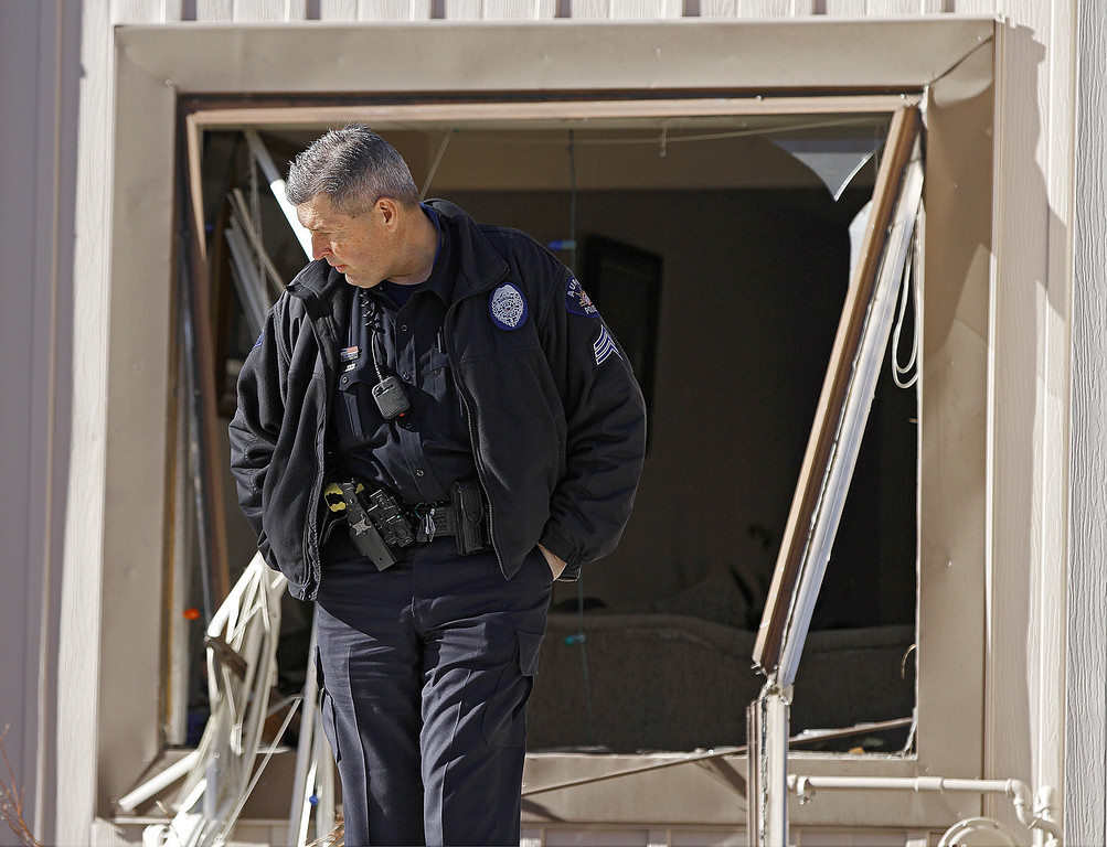 . A police officer stands watch in front of a broken out window in a town home where four people were killed Saturday morning including the gunman who held police at bay for several hours at the complex January 5, 2013 in Aurora, Colorado. Aurora SWAT team members shot a gunman after he went to a second-floor window and fired at police. The gunman also allegedly fatally shot two men and a woman that he had taken hostage. One woman managed to escape from an upstairs back window, ran from the home and called police just before 3 a.m., said Cassidee Carlson, Aurora police spokeswoman.  (Photo by Marc Piscotty/Getty Images)