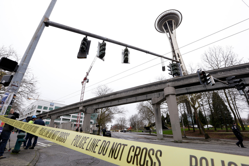 . With the KOMO-TV broadcast building at left, authorities attend to the scene of a news helicopter crash near the Space Needle, Tuesday, March 18, 2014, in Seattle. Two people were killed and another critically injured. (AP Photo/Elaine Thompson)