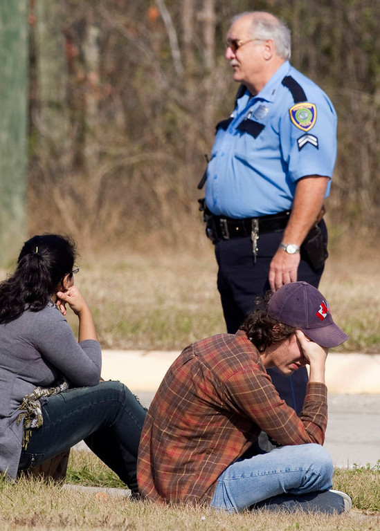 . Lone Star College students sit on the street corner after they were evacuated from the campus following a shooting at the north Harris County school Tuesday, Jan. 22, 2013, in Houston. The shooting wounded three people and sent students fleeing for safety as officials placed the campus on lockdown, officials said. (AP Photo/Houston Chronicle, Brett Coomer)