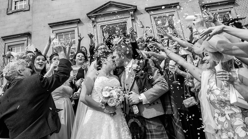 Wedding Photography of Louise & Jason, Dumfries House, Cumnock , Photography is of The Bride & Groom kissing under a shower of confetti