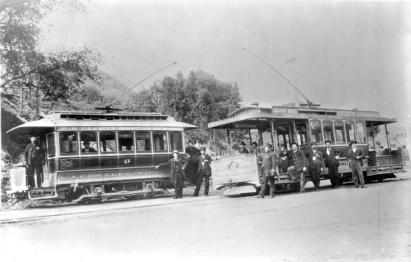 Portrait of people posed around two electric streetcars at Sycamore Park, ca.1895