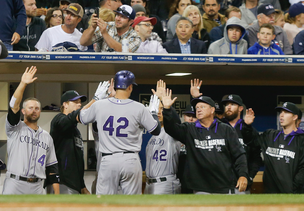 . Colorado Rockies\' Nolan Arenado is greeted at the dugout after he drove in a run against the San Diego Padres with a sacrifice fly in the fourth inning of a baseball game Tuesday, April 15, 2014, in San Diego. (AP Photo/Lenny Ignelzi)