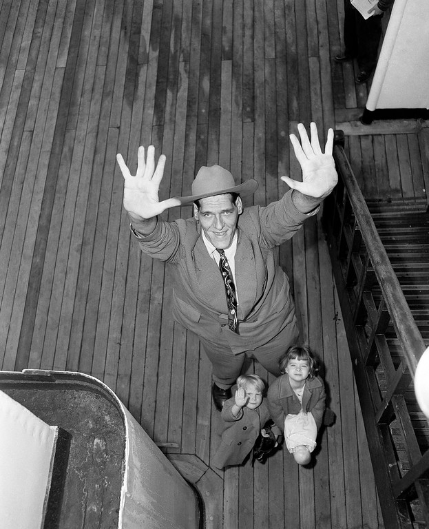 . Ted Evans, 27-year-old circus performer from Derbyshire, England, towers over two fellow passengers as they arrive in New York, March 27, 1952 on the Queen Mary. Evans, who is nine feet, three inches tall and weighs 400 lbs, plans to tour with the Ringling Brothers, Barnum & Bailey Circus. The youngsters are John Brodie, 5 and his sister, Stephanie, 6, en route with their parents to Salt Lake City, Utah. (AP Photo/Anthony Camerano)