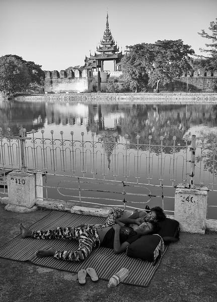 Brother and sister taking a nap on the street with the palace in the background..  Mandalay, Myanmar 2017