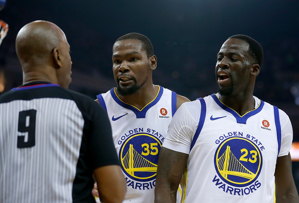 . Golden State Warriors forward Kevin Durant (35) and forward Draymond Green (23) argue a call with referee Derrick Stafford (9) during the first half against the Cleveland Cavaliers of an NBA basketball game in Oakland, Calif., Monday, Dec. 25, 2017. (AP Photo/Tony Avelar)
