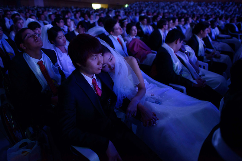 ". Couples watch a performance during a mass wedding event held by the Unification Church in Gapyeong on February 12, 2014. Unification Church members forming 2500 couples from 52 countries were married in a mass wedding in South Korea -- only the second such event since the death of their ""messiah\"" and controversial church founder Sun Myung Moon. (ED JONES/AFP/Getty Images)"