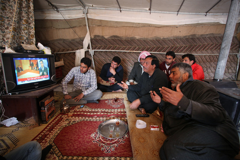 . Syrian refugees watch the news of the peace talks in Switzerland, inside a makeshift tent home in an unofficial refugee camp on the outskirts of Amman, Jordan, Wednesday, Jan. 22, 2014. Peace talks intended to carve a path out of Syria\'s civil war got off to a rocky start Wednesday as a bitter clash over President Bashar Assad\'s future threatened to collapse the negotiations even before they really begin. Later this week in Geneva, Syria\'s warring sides will sit down for their first face-to-face meeting since the conflict erupted. (AP Photo/Mohammad Hannon)