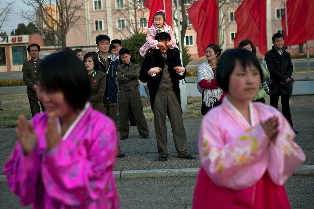 . A North Korean child covers the eyes of her father as she sits on his shoulders watching mass folk dancing in front of Pyongyang Indoor Stadium in Pyongyang, North Korea, on Monday, April 15, 2013. Oblivious to international tensions over a possible North Korean missile launch, Pyongyang residents spilled into the streets Monday to celebrate a major national holiday, the birthday of their first leader, Kim Il Sung. (AP Photo/David Guttenfelder)