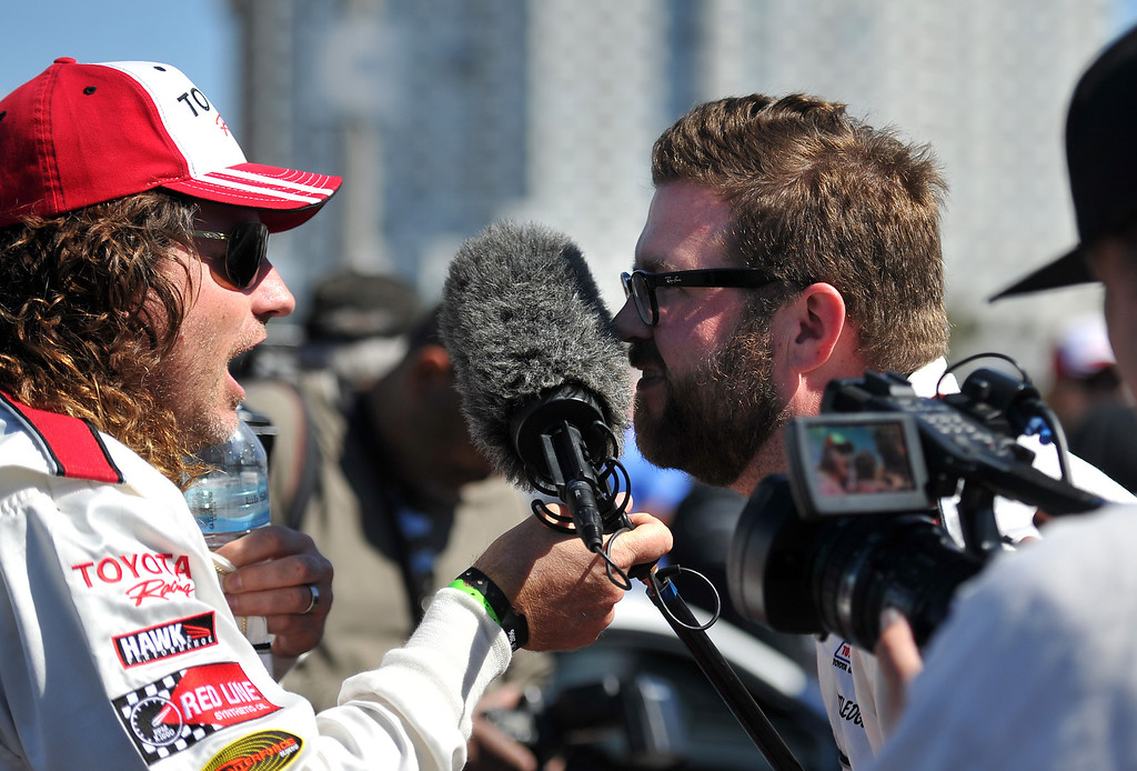 . 4/9/13 - L-R Andy Bell and Rutledge Wood joke around with a sound boom during an interview on media day for the 39th Annual Toyota Grand Prix of Long Beach. The celebrity/pro races spent the day practicing on the track, joking with their racing partners and giving interviews. Photo by Brittany Murray / Staff Photographer
