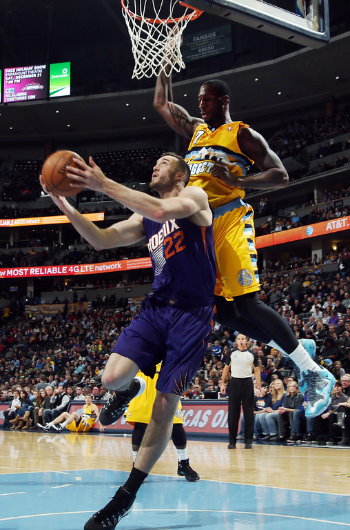 . Phoenix Suns center Miles Plumlee, bottom, is fouled as he goes up for a shot by Denver Nuggets forward J.J. Hickson in the first quarter of an NBA basketball game in Denver on Friday, Dec. 20, 2013. (AP Photo/David Zalubowski)