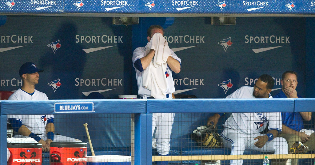 . Toronto Blue Jays pitcher Casey Janssen stands in the dugout mopping his brow after he gave up three runs and the lead to the Detroit Tigers in the ninth inning of a baseball game, Friday, Aug. 8, 2014 in Toronto. (AP Photo/The Canadian Press, Fred Thornhill)