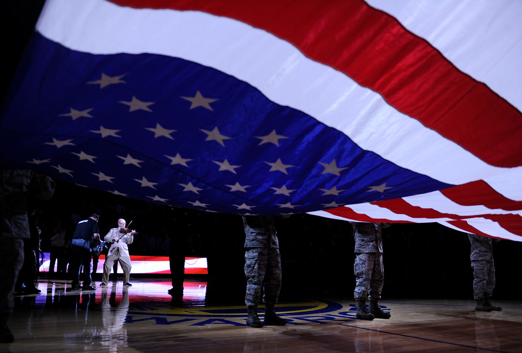 . Members of the Air National Guard hold the up the American flag as the national anthem is played before the Golden State Warriors take on the Miami Heat on Wednesday, Jan. 16, 2013, at Oracle Arena in Oakland, Calif. (Susan Tripp Pollard/Staff)