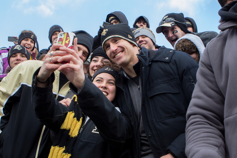 A studet takes a picture with Drew Brees in the student section during the fourth quarter of the Purdue game