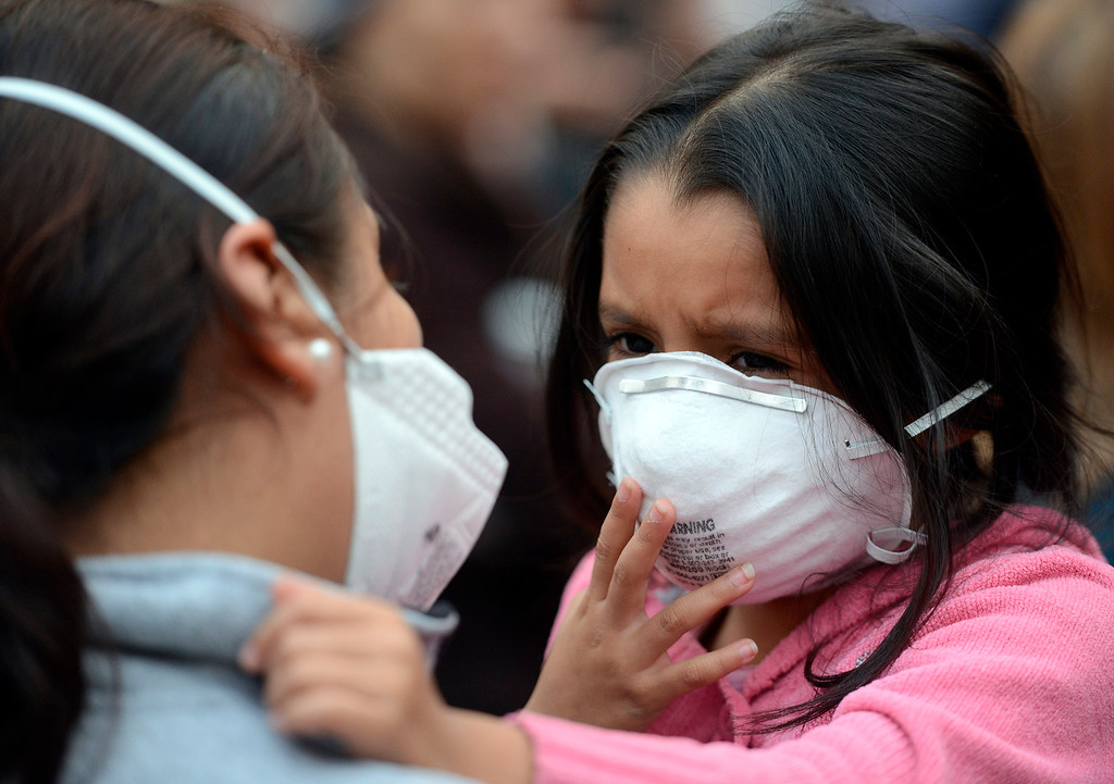 . Daniela Esparza, 5, and her mother Soledad wear masks to protect themselves from smoke and ash as they listen to a briefing on the fire at the Big Sur Station in Big Sur, Calif. on Tuesday December 17, 2013. (Photo David Royal/ Monterey County Herald)