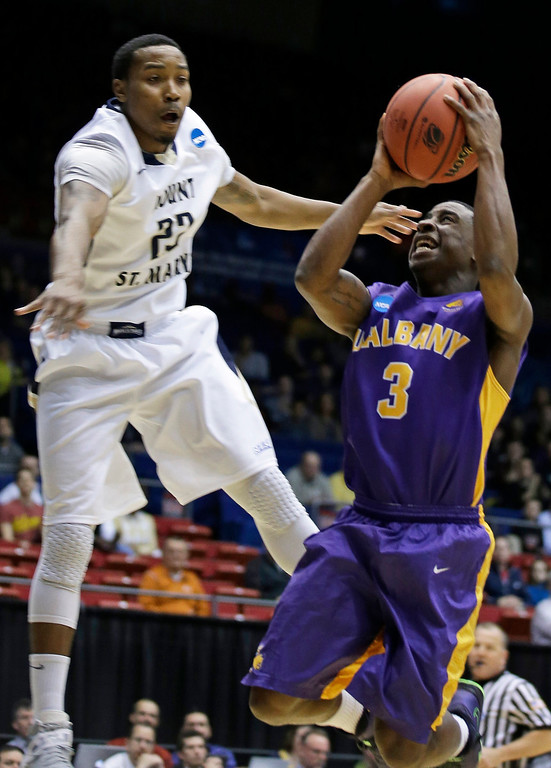 . Albany guard DJ Evans (3) drives against Mount St. Mary\'s guard Julian Norfleet in the first half of a first-round game of the NCAA college basketball tournament, Tuesday, March 18, 2014, in Dayton, Ohio. (AP Photo/Al Behrman)