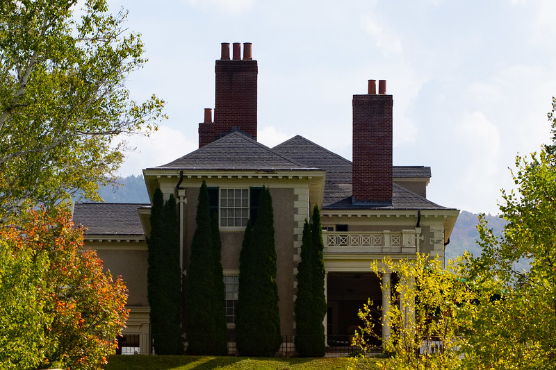 image of large house with three chimneys surrounded by fall foliage.