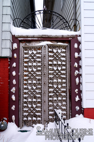 Snow on an ornate gate.