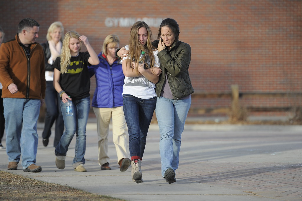 . CENTENNIAL, CO -  A student leaves Euclid Middle School with their parents after getting bused their from Arapahoe High School December 13, 2013. A gunman at the school was targeting a teacher at the school. The gunman shot two students in the process and then turned the gun on himself. (Photo by John Leyba/The Denver Post)