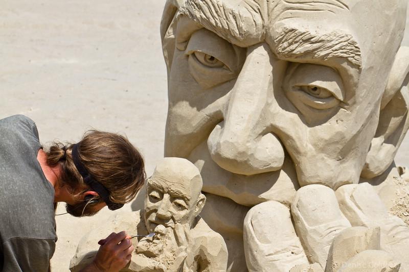 Carl Jara working on his sculpture, a man holding a man holding a man