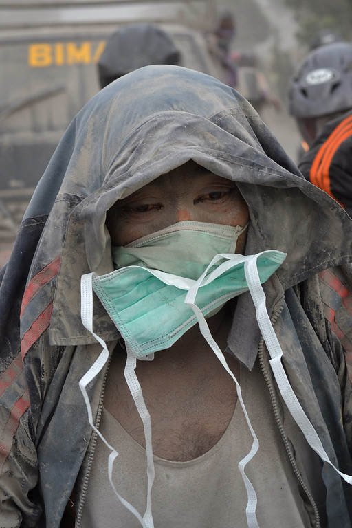 . A man wearing a mask for protection from volcanic ash arrives at an evacuation center in Malang, East Java province on February 14, 2014. AFP PHOTO / AMAN ROCHMAN/AFP/Getty Images