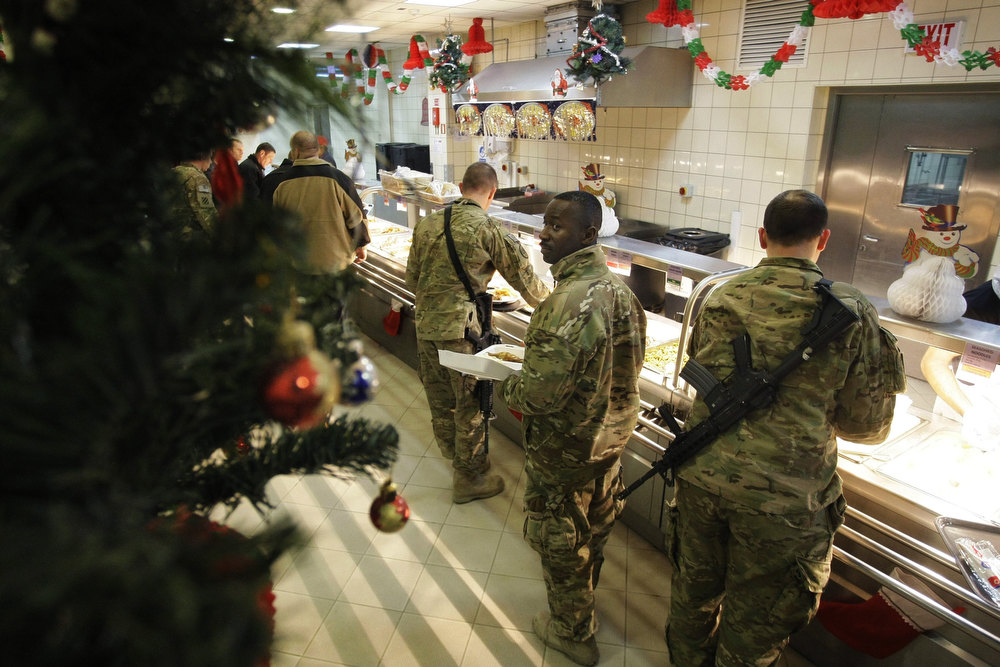 . U.S. soldiers and service members with the NATO-led International Security Assistance Force (ISAF) wait to get food at a dinning hall on Christmas eve at the U.S.-led coalition base in Kabul, Afghanistan, Monday, Dec. 24, 2014. (AP Photo/Musadeq Sadeq)