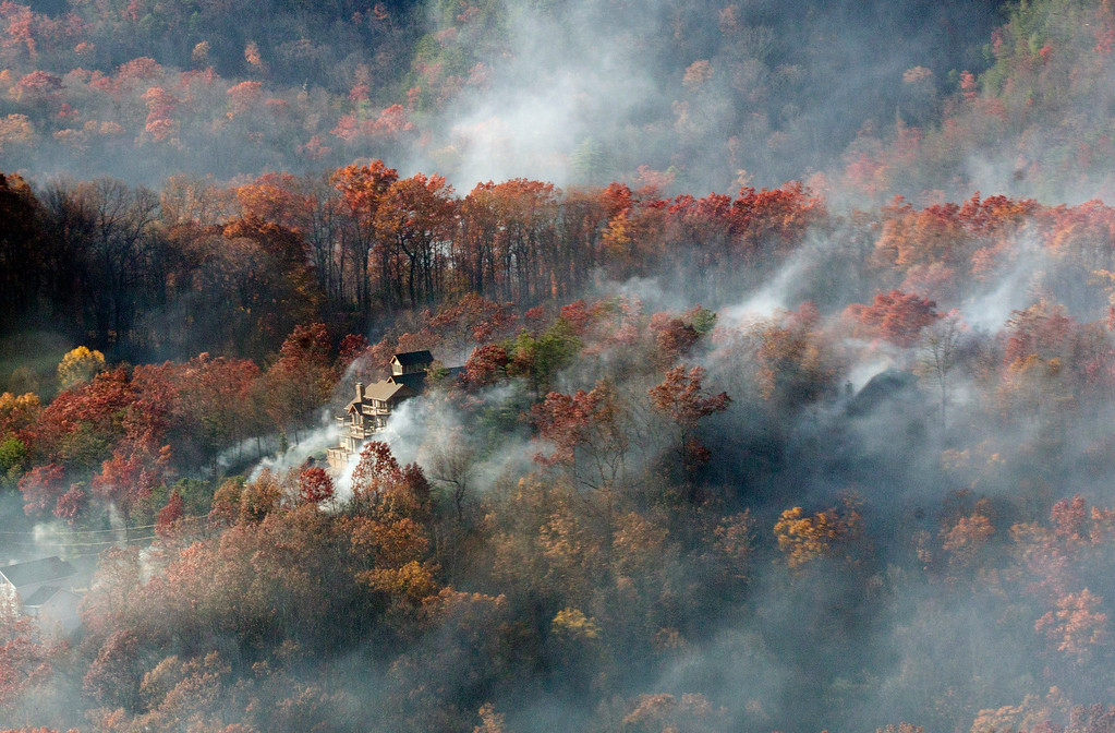 . Smoke surrounds a home as seen from aboard a National Guard helicopter near Gatlinburg, Tenn., Tuesday, Nov. 29, 2016. Thousands of people have fled deadly wildfires that have destroyed hundreds of homes and a resort in the Great Smoky Mountains. (AP Photo/Erik Schelzig)