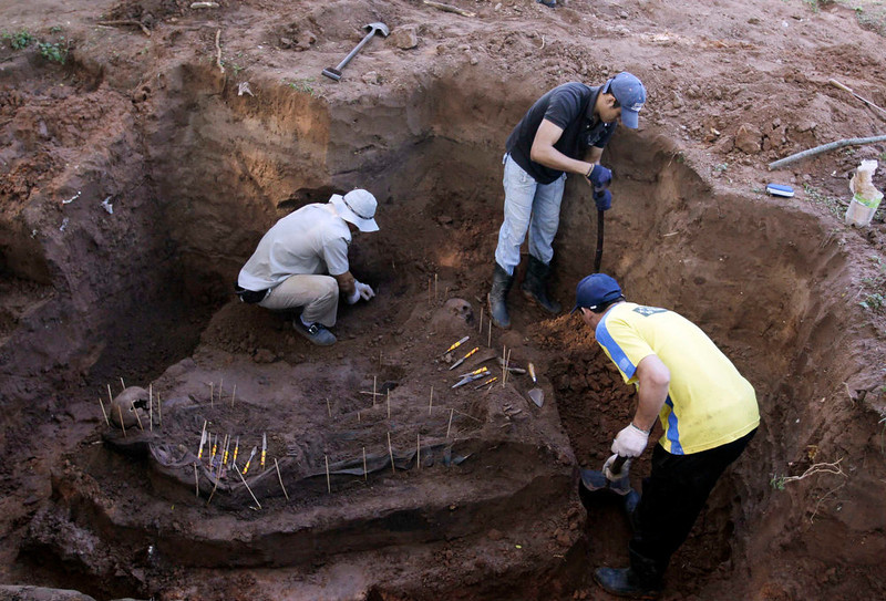 . Members of the police assist in excavating human remains discovered in the grounds of a police barracks in Asuncion, Paraguay on March 21, 2013. According to the researchers, 15 more skeleton remains, likely to be victims of the 1954 to 1989 dictatorship under Alfredo Stroessner, were found in the last two days.  REUTERS/Jorge Adorno