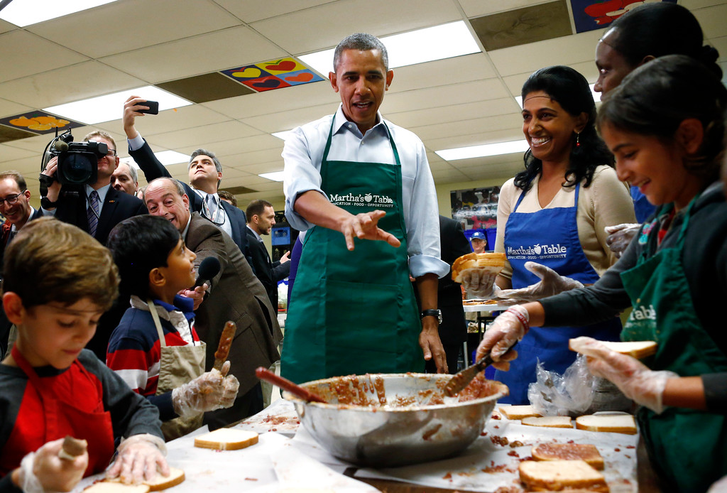 ". President Barack Obama stops by a table of grade school aged volunteers making peanut butter and jelly sandwiches as he visits Martha\'s Table, which assists the poor and where furloughed federal employees are volunteering, in Washington, Monday, Oct. 14, 2013. Speaking there Obama said that if Republicans can\'t resolve the standoff over the debt ceiling and the partial government shutdown, quote, ""we stand a good chance of defaulting.\"" (AP Photo/Charles Dharapak)"