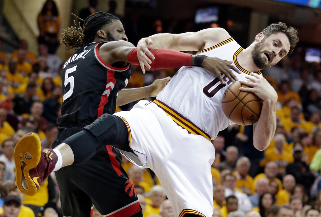 . Toronto Raptors\' DeMarre Carroll (5) puts pressure on Cleveland Cavaliers\' Kevin Love (0) in the first half in Game 1 of a second-round NBA basketball playoff series, Monday, May 1, 2017, in Cleveland. (AP Photo/Tony Dejak)