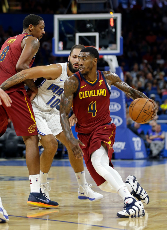 . Cleveland Cavaliers\' Iman Shumpert (4) drives past Orlando Magic\'s Evan Fournier, center, during the first half of an NBA preseason basketball game, Friday, Oct. 13, 2017, in Orlando, Fla. (AP Photo/John Raoux)