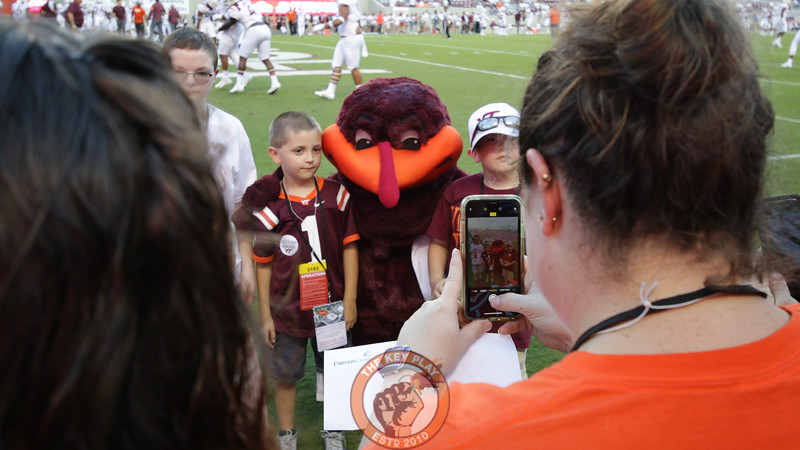 The Hokiebird poses with fans on the field as they get their picture taken during pre-game warmups. (Mark Umansky/TheKeyPlay.com)
