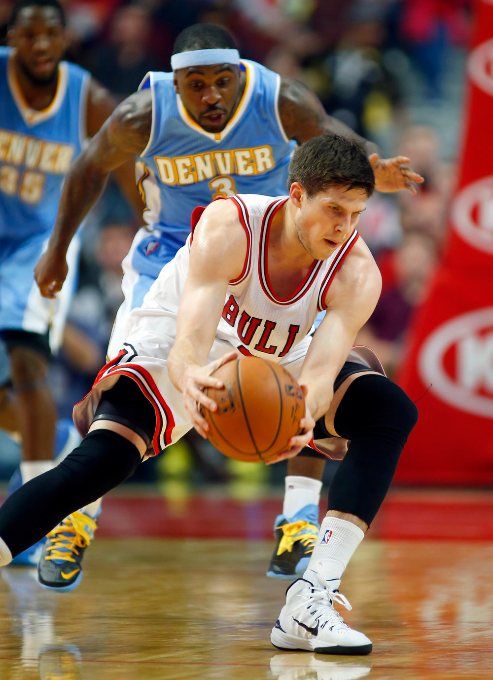 . Chicago Bulls forward Doug McDermott (3) grabs a lose ball against the Denver Nuggets during the first half of a pre-season NBA basketball game in Chicago, on Monday Oct. 13, 2014. (AP Photo/Jeff Haynes)