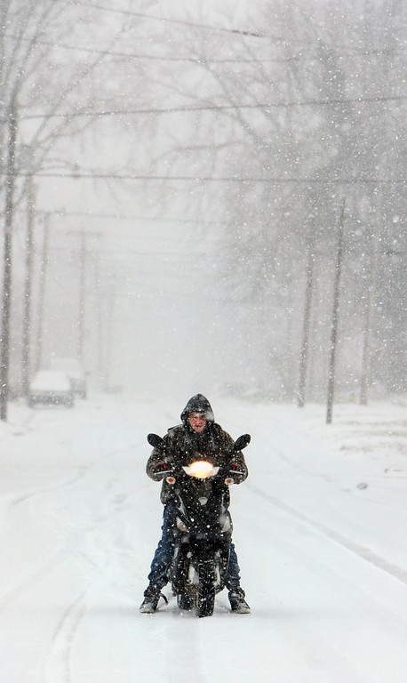 . Jesse Ray, 16, rides his moped to a friend\'s house on Friday, Dec. 6, 2013, in Owensboro, Ky. A wintry mix struck the western part of Kentucky first but was moving eastward by Friday afternoon, and much of the eastern half of the U.S. was blanketed in precipitation. (AP Photo/The Messenger-Inquirer, John Dunham)