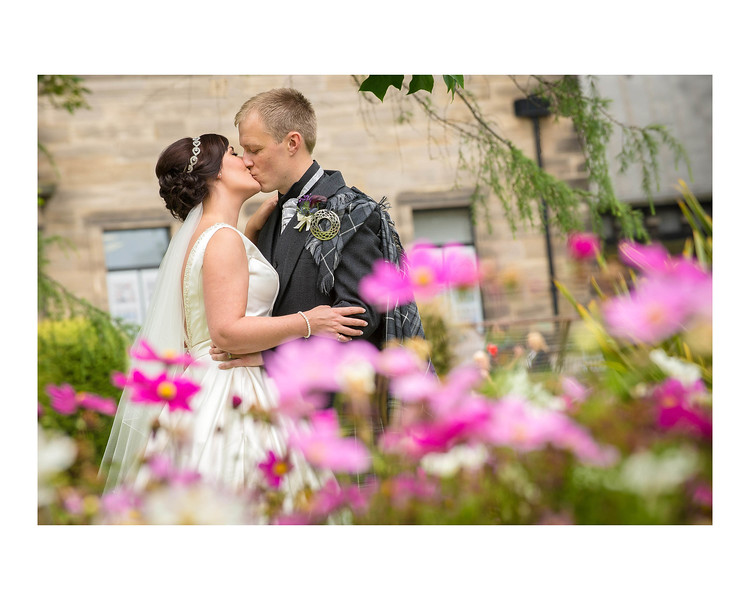 Wedding Photography of Laura & Kevin, Dean Park Hotel, Kirkcaldy, Fife, Scotland, Photograph is of the Bride & Groom standing and kissing behind colourful flowers