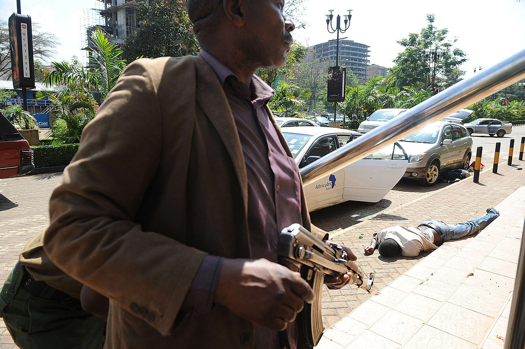 . A body of a man lies on the ground as armed policemen try to get entry into the Westgate after masked gunmen stormed an upmarket mall and sprayed gunfire on shoppers and staff, killing at least six on September 21, 2013 in Nairobi. The Gunmen have taken at least seven hostages, police and security guards told an AFP reporter at the scene. AFP PHOTO/SIMON MAINA/AFP/Getty Images