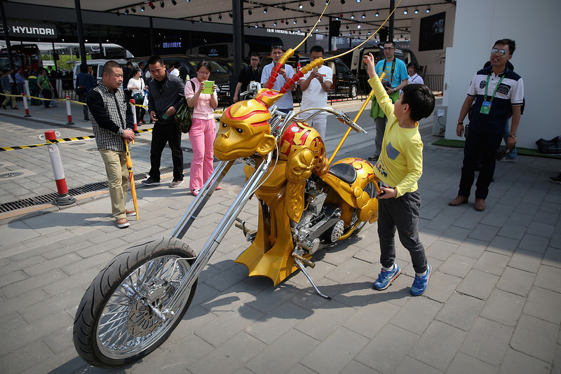 . A Chinese little boy touches the Monkey King motorcycle during the 2014 Beijing International Automotive Exhibition at China International Exhibition Center on April 22, 2014 in Beijing, China. More than 2,000 automotive enterprises from 14 countries and regions participated in the 2014 Beijing International Automotive Exhibition from April 20 to April 29.  (Photo by Feng Li/Getty Images)