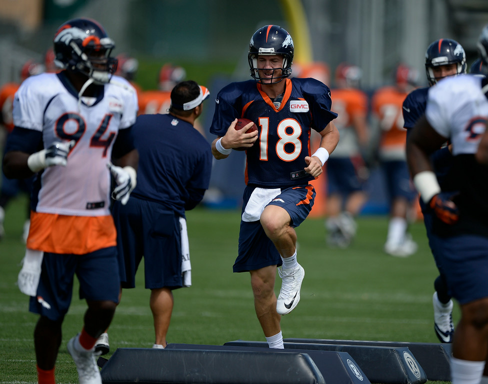 . Denver Broncos quarterback Peyton Manning (18) runs through drills during practice August 26, 2014 at Dove Valley.(Photo by John Leyba/The Denver Post)