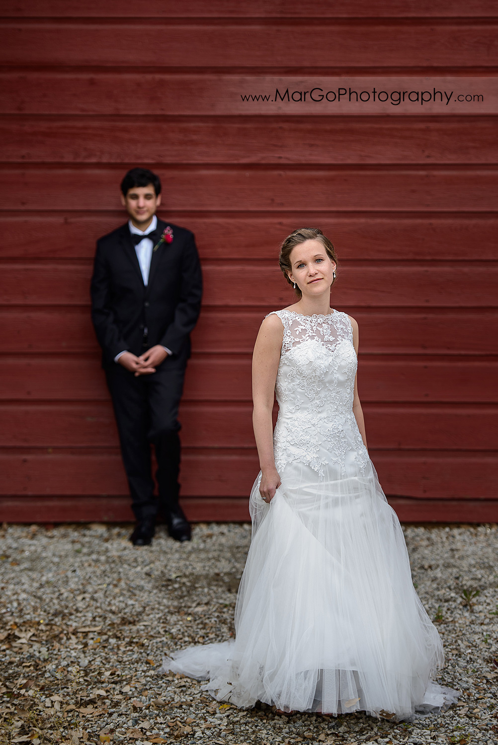 bride astanding in front of groom looking on the red barn wall during bridal session at Shinn Historical Park and Arboretum in Fremont