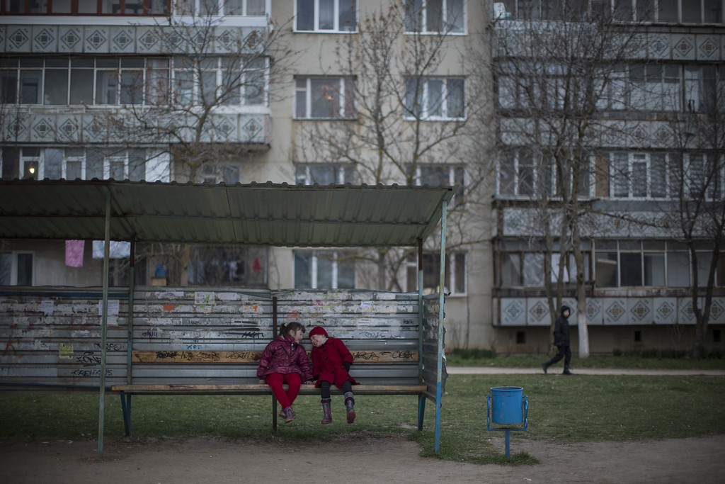 . Girls sit in a bus stop in a residential estate next to a Ukrainian military base on March 12, 2014 in Simferopol, Ukraine. As the standoff between the Russian military and Ukrainian forces continues in Ukraine\'s Crimean peninsula, world leaders are pushing for a diplomatic solution to the escalating situation. Crimean citizens will vote in a referendum on 16 March on whether to become part of the Russian federation.  (Photo by Dan Kitwood/Getty Images)