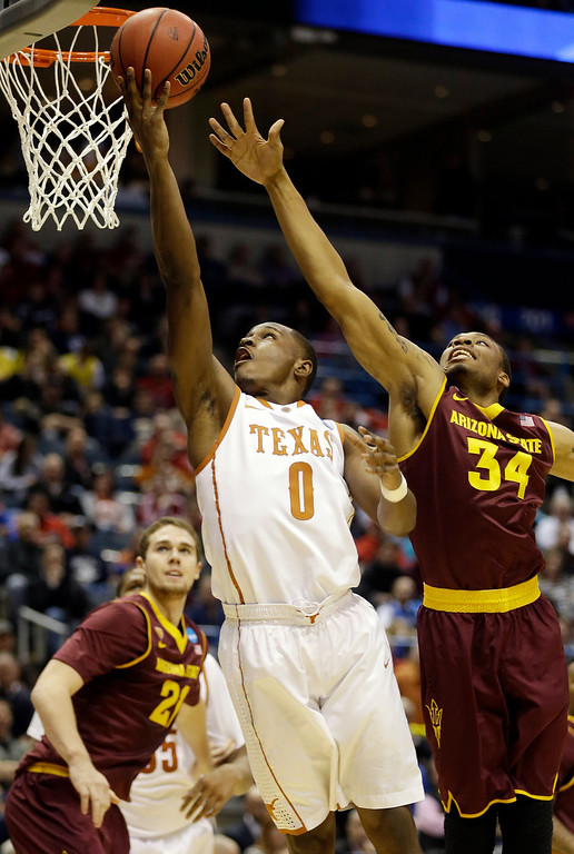 . Texas guard Kendal Yancy (0) goes up for a shot against Arizona State guard Jermaine Marshall (34) during the first half of a second-round game in the NCAA college basketball tournament Thursday, March 20, 2014, in Milwaukee. (AP Photo/Jeffrey Phelps)