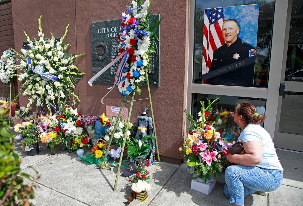 . Hayward resident Hilda Sierra moves some flowers under the portrait of fallen Sgt. Scott Lunger outside the Hayward Police Department in Hayward, Calif., on Wednesday, July 22, 2015. Lunger was shot and killed early Wednesday morning during a routine traffic stop. (Laura A. Oda/Bay Area News Group)