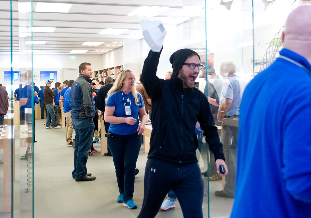 . Rob Beckett, center, of Portland, Mich., is met with cheers and applause as the first person to leave with a brand new iPhone 6 from the Apple Store at the Woodland Mall on Friday, Sept. 19, 2014 in Grand Rapids, Mich.  The highly anticipated iPhone 6 and iPhone 6 Plus are being released in stores today. (AP Photo/The Grand Rapids Press, Emily Rose Bennett)