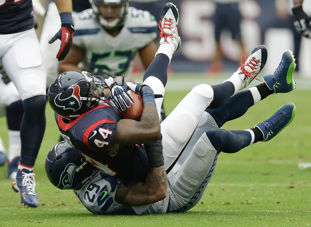 . Houston Texans\' Ben Tate (44) is stopped by Seattle Seahawks\' Earl Thomas (29) during the first quarter an NFL football game Sunday, Sept. 29, 2013, in Houston. (AP Photo/David J. Phillip)