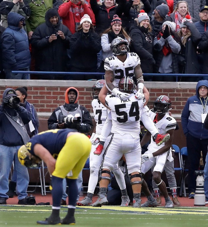 . Ohio State running back Mike Weber (25) is lifted by offensive lineman Billy Price (54) after scoring during the second half of an NCAA college football game against Michigan, Saturday, Nov. 25, 2017, in Ann Arbor, Mich. (AP Photo/Carlos Osorio)