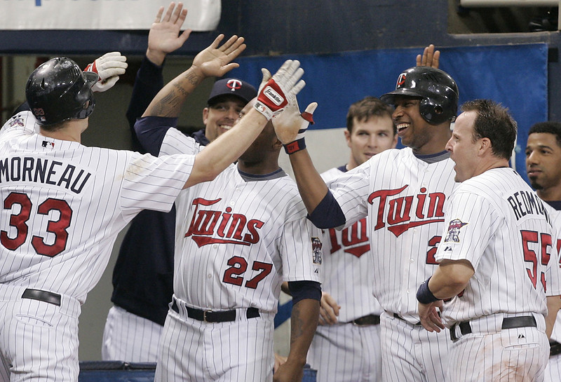 . The Twins\' Justin Morneau, left, is greeted by teammates after he tripled and then scored on an error by New York Yankees center fielder Melky Cabrera in sixth inning of their game Sunday, June 1, 2008 in Minneapolis. (AP Photo/Jim Mone)