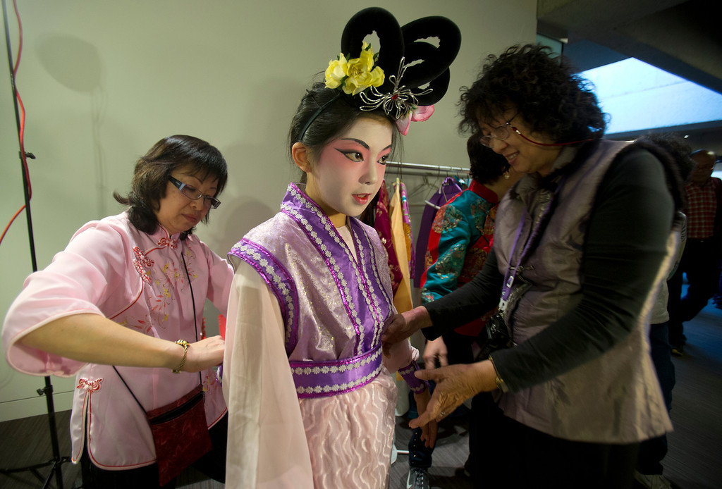 . Ten-year-old Joanne Low of Oakland, Calif., center, gets the final touches put on her Chinese opera costume while attending the Oakland Museum of California\'s Lunar New Year celebration, Sunday, Feb. 17, 2013 in Oakland. Visitors to the museum were treated to a wide variety of Asian traditions, including dance, food, music, calligraphy, martial arts, story-telling and more. (D. Ross Cameron/Staff)