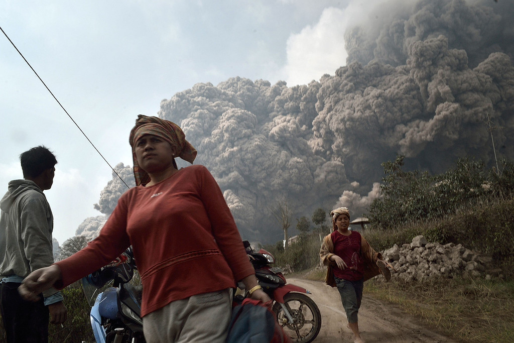 . Residents run away to escape from hot volcanic ash clouds engulfing villages in Karo district during the eruption of Mount Sinabung volcano located in Indonesia\'s Sumatra island on February 1, 2014. AFP PHOTO / SUTANTA ADITYA/AFP/Getty Images