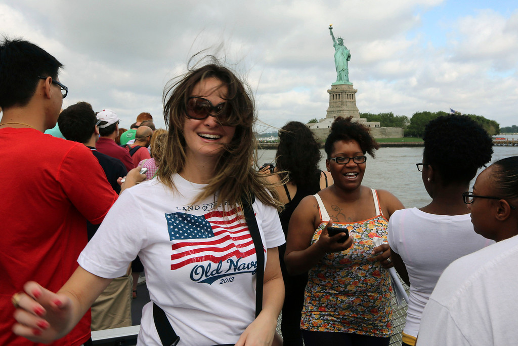 . Visitors to fhe Statue of Liberty take photos as they arrive on the first tourist ferry to leave Manhattan, Thursday, July 4, 2013, in New York. The Statue of Liberty finally reopened on the Fourth of July months after Superstorm Sandy swamped its island in New York Harbor as Americans across the country marked the holiday with fireworks and barbecues. (AP Photo/Mary Altaffer)